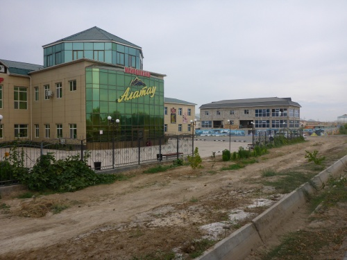 Kyzylorda Abai Avenue - but could be any town, some new flash building with grand entrance that cannot be used and dirt road approach with unfinished building next door, all boarded up.
