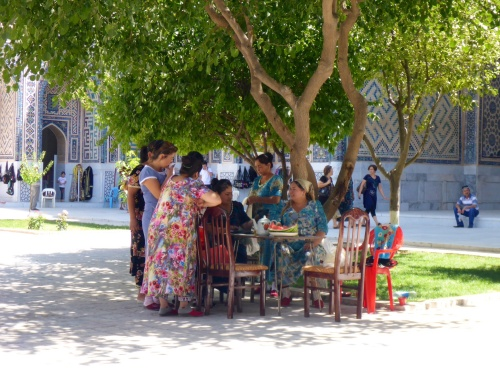Uzbek family having lunch inside Ulugh-Beg madrasah, Registan, Samarkand, Uzbekistan