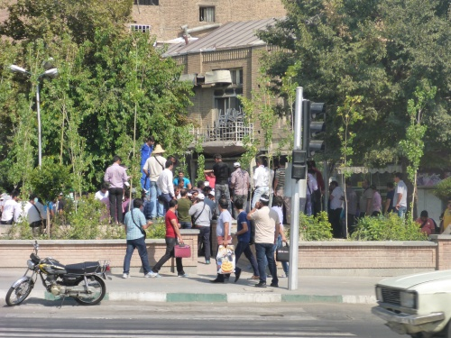 Illegal currency trading occurs openly, opposite police guarding the old UK embassy in Tehran, Iran