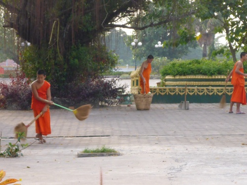 Monks brushing up leaves at Pha That Luang, Vientiane, laos