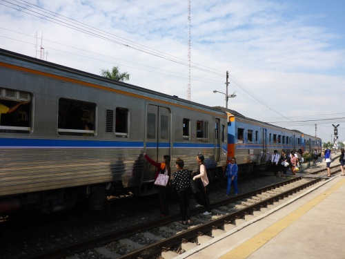A modern train with closing doors is boarded from both sides at Ayutthaya station