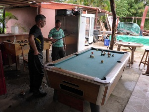 Anthony has a game of pool with one of the restaurant staff