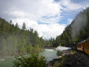Engine discharges steam by the Animas river